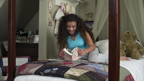 Slow motion of girl reading book on her bed Live Action