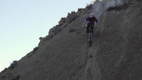 Slow motion of guy riding mountain bike down steep dirt hill Footage