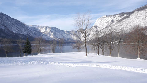 Aerial - Snow path beside a lake. Snow-capped mountains in the background Footage