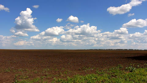 Blue sky with clouds over plowed field Footage
