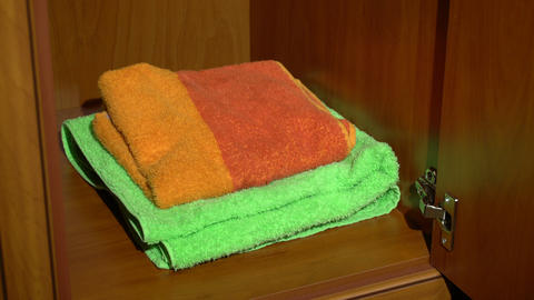 Placing a set of towels into a wardrobe Live Action