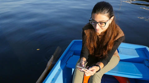 Beautiful girl sitting in a boat with a phone. Slow motion. Beautiful waves on Footage