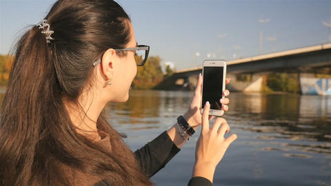 The girl makes a photo on the phone. Beautiful nature. River with a bridge Live Action