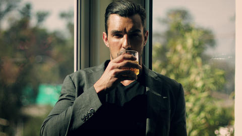 Handsome man having a drink GIF