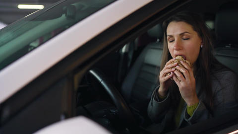 Woman eating sandwich sitting in the car on the parking. Concept of a modern Footage