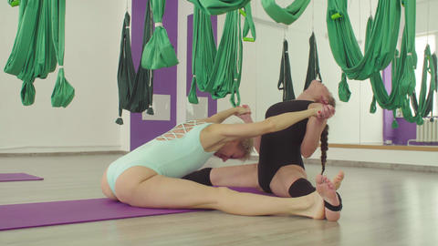 Two attractive flexible women doing yoga exercises in pair Live Action