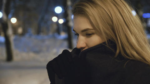 Profile of a young woman who freezes at night in the street Steam comes out of Live Action