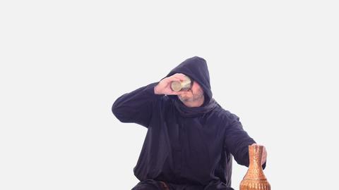 drunken medieval man in hoodie drinks vine white screen Footage