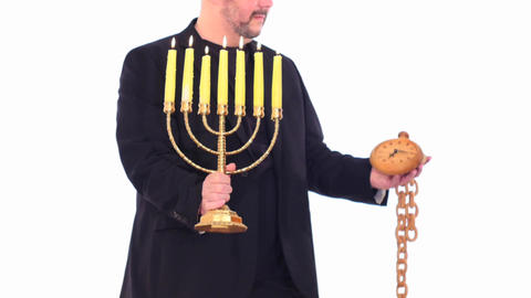 Man in kippah keeping Menorah & fast running clock white screen follow focus - Judaism saved through Footage