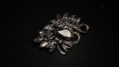 Brooch in with stones on a black rotating stand. Premium Jewelery. Macro Footage