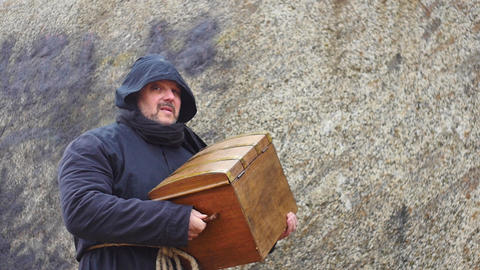 medieval man in hoodie bringing antique chest slow motion Live Action