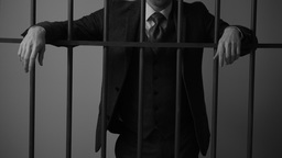 An insolent white collar criminal behind bars in prison Footage