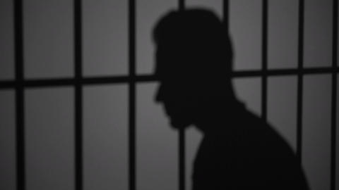 Shadow silhouette of an inmate behind bars Footage