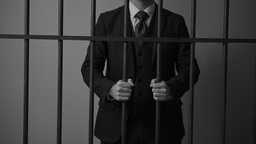 White collar criminal grips bars in a prison cell Footage