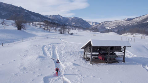 Aerial - Child running across snow covered field, slow motion Footage