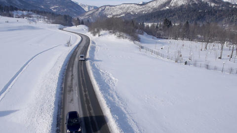 Aerial - Cars driving on a two-lane road through a snowy landscape Footage