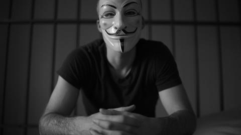 Anonymous hacker in prison glares at camera (B/W Version) Footage
