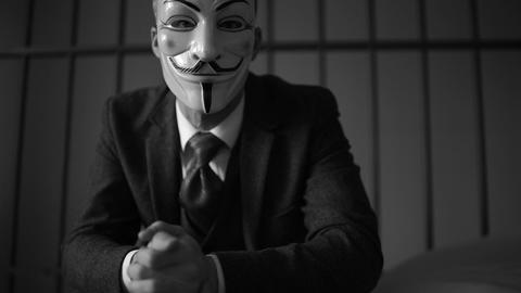 Anonymous hacker seated in prison (B/W Version) Footage