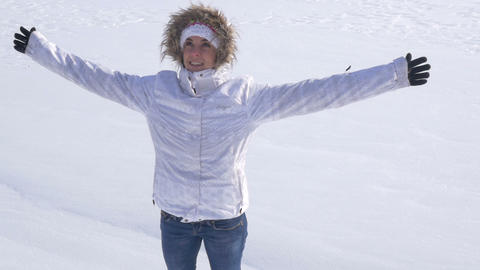 Young woman raises hands and falls back into the snow Footage