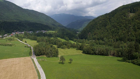 Aerial - Valley among the hills with various types of fields and a car road Footage