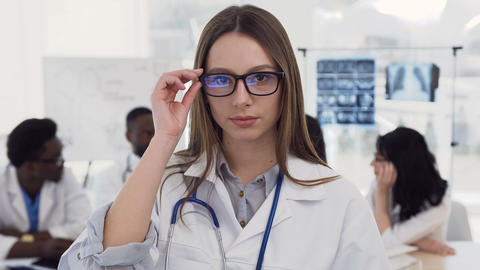 Portrait of confident female medical doctor in glasses and white coat with Live Action