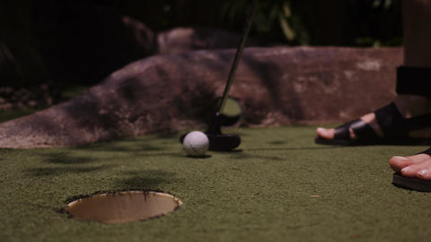 A young woman playing mini golf. Legs in the frame. Mid shot. Shoot Ball in the Live Action