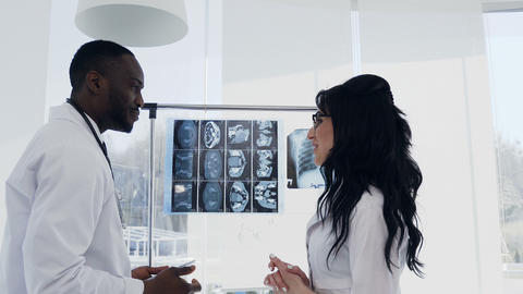 Two doctors are looking at x-rays. Medical. Chief physician afro american man Live Action