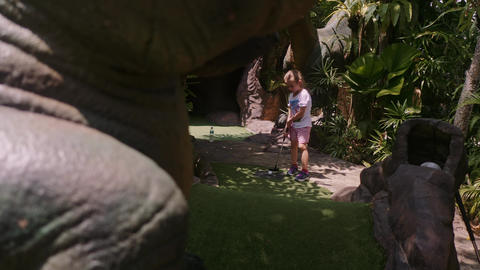 Playful Childhood. Little Girl Play Mini Golf Outdoor Live Action
