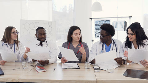 Team of multiethnic young doctors having a meeting in conference room in the Footage