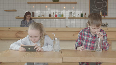 Kids playing online games on cellphones at cafe Live Action