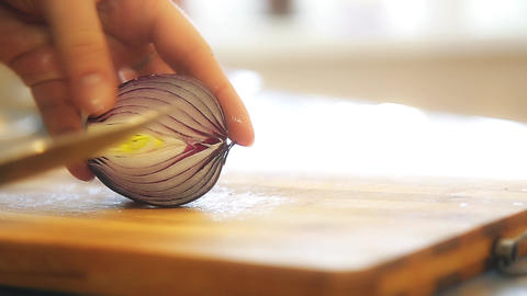 A woman in the village of finely cut red onions on a kitchen cutting Board Footage