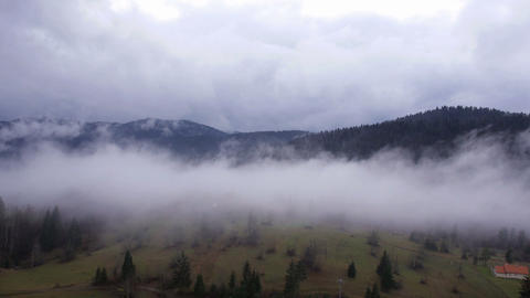 Aerial - Foggy clouds roll over valley ridges Footage