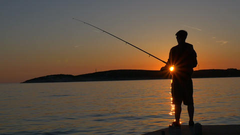 Slow motion - Young fisherman standing on pier at sunset Footage