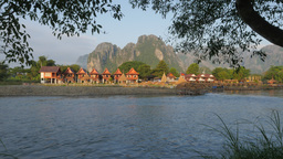 Karst mountains and bungalows with jogger,Vang Vieng,Laos Footage