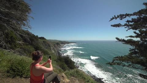 Crane shot of woman hiker photographing Big Sur coastline Footage