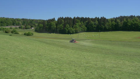 Aerial - Tractor Turning The Grass To Make Hay stock footage