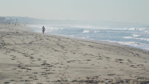 Surfer walks beach near the Santa Monica Pier Footage