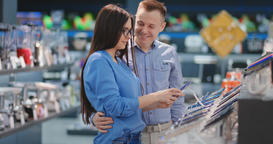 Happy couple looking at a new digital camera at an electronics shop Footage