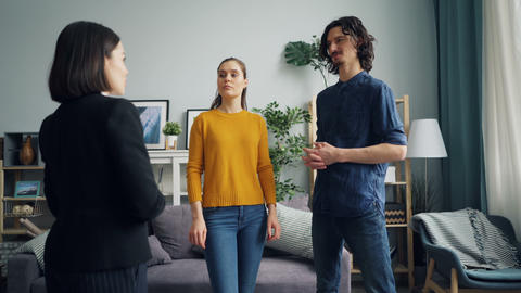 Man talking to realtor while wife looking at new flat standing indoors together Footage