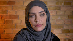 Closeup portrait of adult attractive muslim female in hijab looking at camera ビデオ
