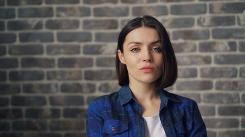 Slow motion portrait of confident young woman looking at camera near brick wall Footage