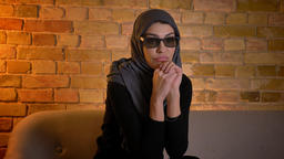 Closeup portrait of adult attractive muslim female in hijab watching a scary 3D Footage
