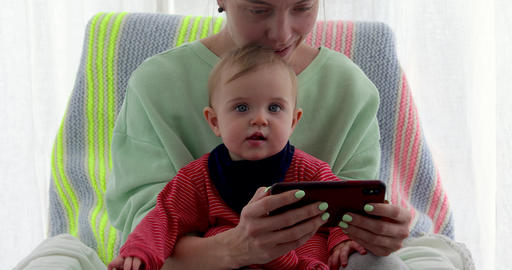 Mother with little daughter seats near the window and uses smartphone Archivo