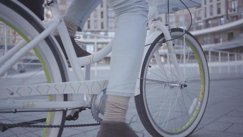 Feet of young man in light blue jeans riding his bicycle in the city close up Footage