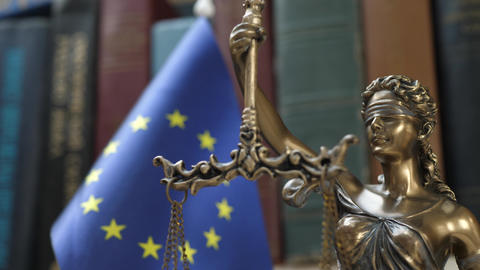 Statue of Lady Justice with Bookshelf with Books and EU Flag Background Footage