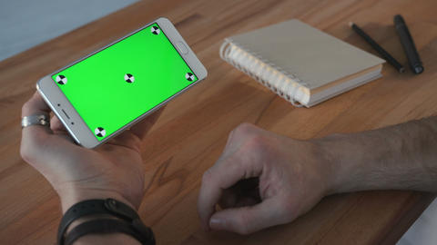 Man using phone with green screen display at desk GIF