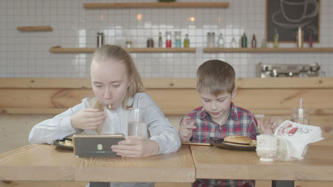 Kids with phones enjoying fast food meal in cafe Footage