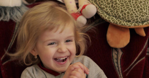 Close up of a little blonde cute girl face. Girl smiling. Inside. Portrait shot Live Action