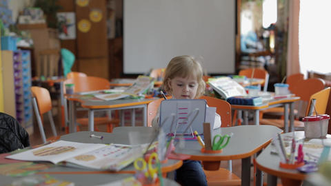 Girl drawing at the table in classroom. Education. Child sitting at a desk Footage