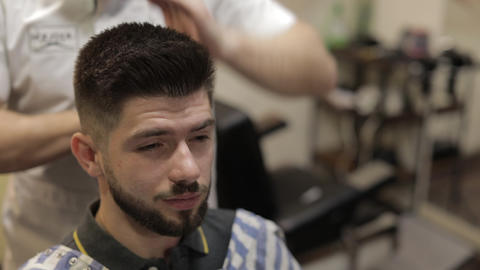 Client with black beard during hair cut in barber shop. Groom, masculine Live Action